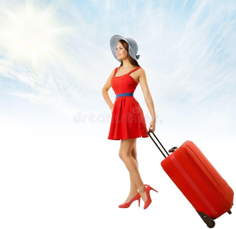 Γυναίκα που τραβά τις κόκκινες αποσκευές βαλιτσών, κορίτσι στο φόρεμα SummerHat στοκ εικόνες με δικαίωμα ελεύθερης χρήσης