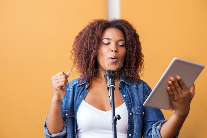 Γυναίκα που τραγουδά ενώ εκμετάλλευση ψηφιακή ταμπλέτα στοκ εικόνες