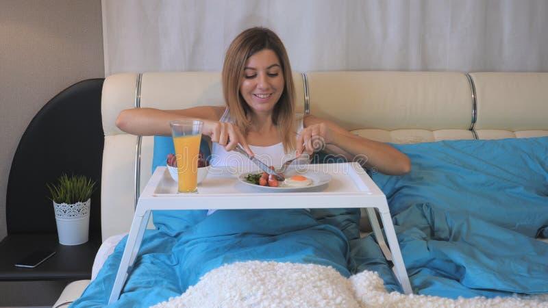 Γυναίκα που τρώει τα λουκάνικα προγευμάτων με τα τηγανισμένα αυγά στον πίνακα, που βρίσκεται στο κρεβάτι στοκ φωτογραφίες