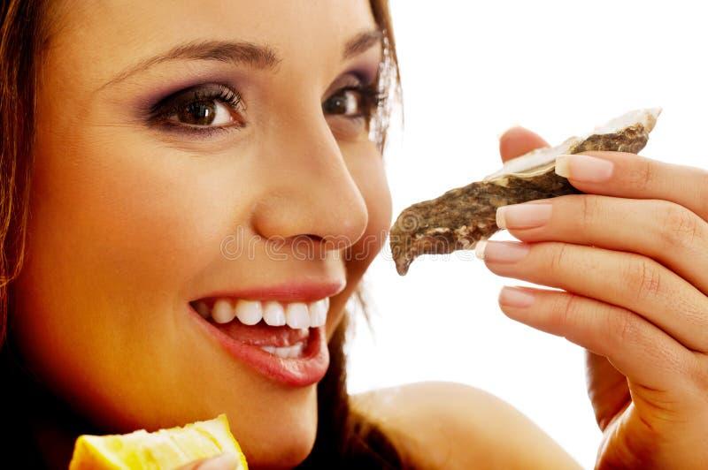 Γυναίκα που τρώει τα οστρακόδερμα στοκ εικόνα