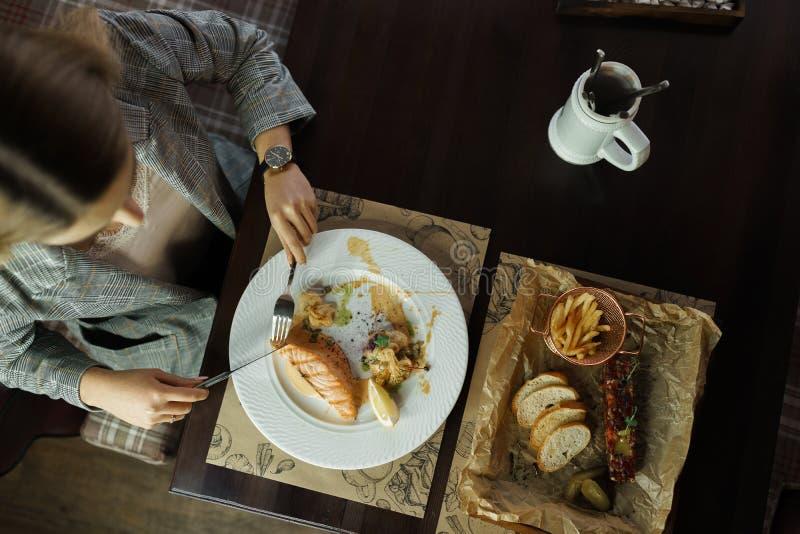 Γυναίκα που τρώει τα υγιή νόστιμα τρόφιμα σε ένα εστιατόριο σε έναν ξύλινο πίνακα μεσημεριανό διάλειμμα τρόπου ζωής Τοπ άποψη του στοκ εικόνες με δικαίωμα ελεύθερης χρήσης