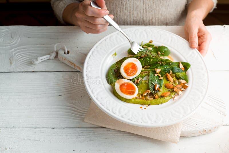 Γυναίκα που τρώει τη σαλάτα με το σπανάκι, το αμύγδαλο και τα αυγά οριζόντια στοκ φωτογραφία