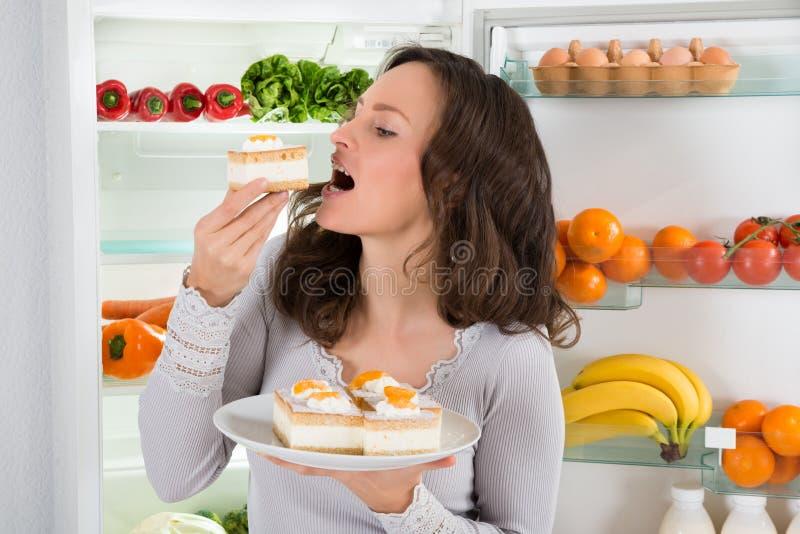 Γυναίκα που τρώει τη φέτα του κέικ στοκ φωτογραφίες