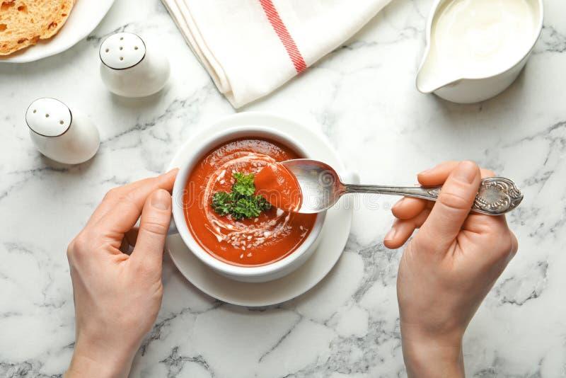 Γυναίκα που τρώει τη φρέσκια σπιτική σούπα ντοματών στο μαρμάρινο πίνακα στοκ φωτογραφίες