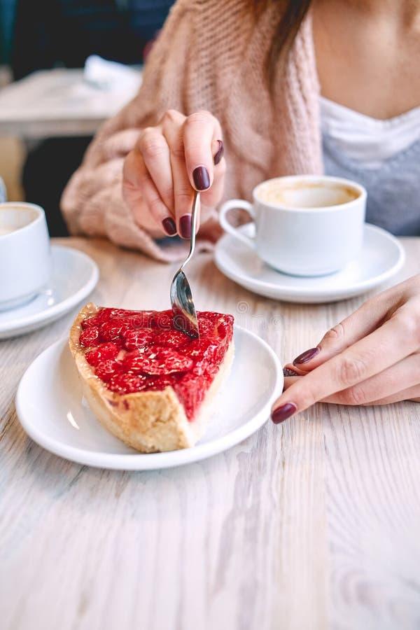 Γυναίκα που τρώει το επιδόρπιο μούρων με ένα κουτάλι στη καφετερία στοκ εικόνες