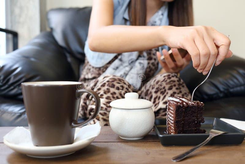Γυναίκα που τρώει το κέικ και τον καφέ σοκολάτας στοκ εικόνα