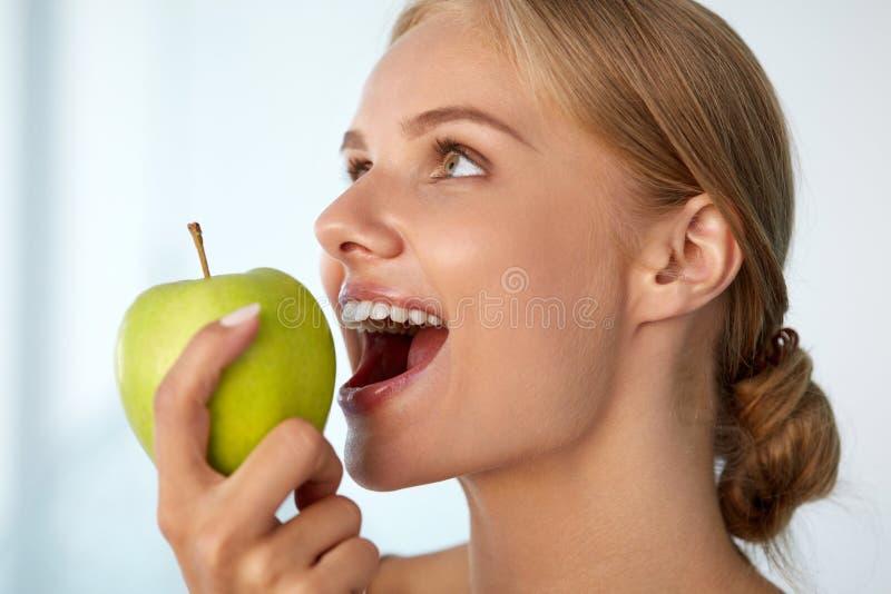 Γυναίκα που τρώει το μήλο Όμορφο κορίτσι με τα άσπρα δόντια που δαγκώνουν τη Apple στοκ φωτογραφία με δικαίωμα ελεύθερης χρήσης