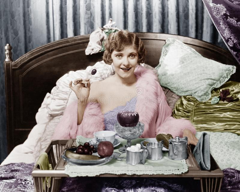 Γυναίκα που τρώει το πρόγευμα στο κρεβάτι (όλα τα πρόσωπα που απεικονίζονται δεν ζουν περισσότερο και κανένα κτήμα δεν υπάρχει Εξ στοκ εικόνες