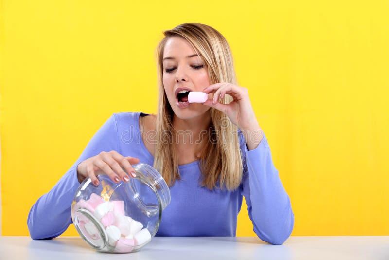 Γυναίκα που τρώει marshmallow στοκ φωτογραφία