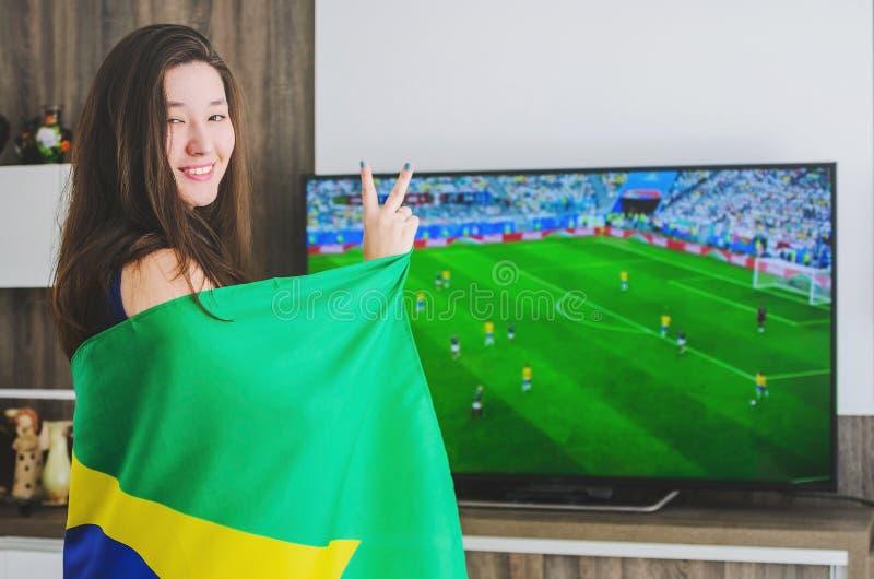 Γυναίκα που τυλίγεται στη βραζιλιάνα σημαία που προσέχει έναν αγώνα από το BR στοκ φωτογραφίες