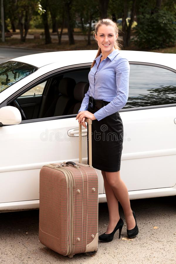 Γυναίκα που υπερασπίζεται το άσπρο αυτοκίνητο με τη μεγάλη βαλίτσα στοκ εικόνες