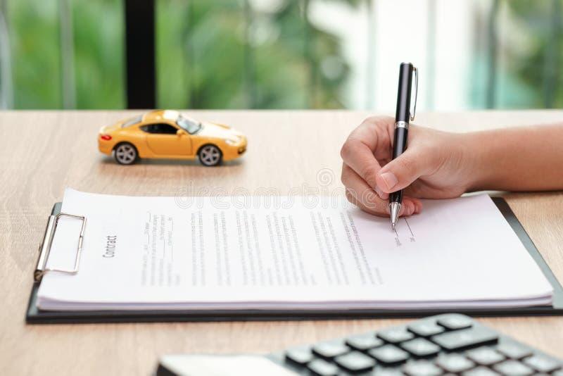 Γυναίκα που υπογράφει τη σύμβαση συμφωνίας δανείου αυτοκινήτων με το παιχνίδι και το calcu αυτοκινήτων στοκ εικόνα