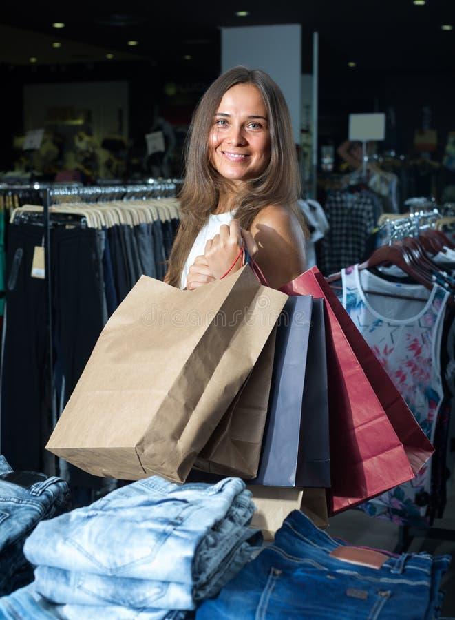 Γυναίκα που φέρνει πολλές τσάντες εγγράφου στοκ εικόνες