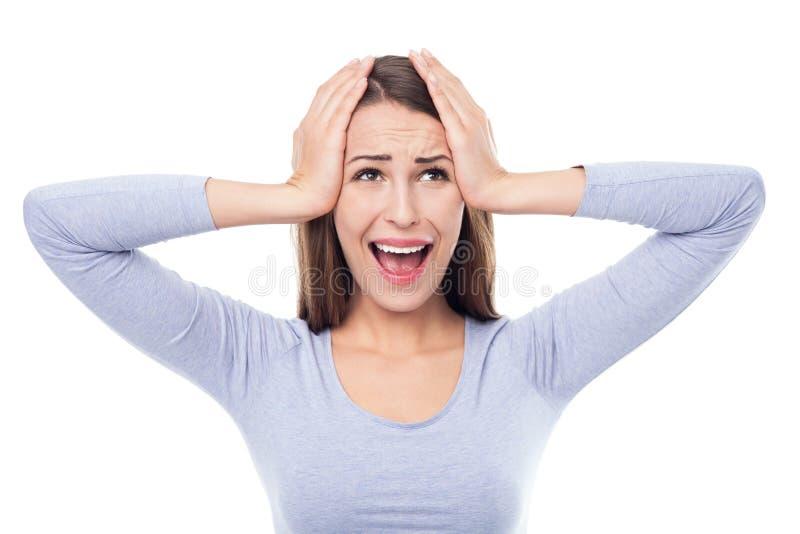 Γυναίκα που φαίνεται έκπληκτη με το κεφάλι της στα χέρια της στοκ εικόνα