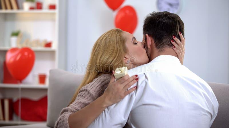 Γυναίκα που φιλά tenderly τον άνδρα, ευγνώμονα για το δώρο βαλεντίνων κοσμήματος, εορτασμός στοκ εικόνες