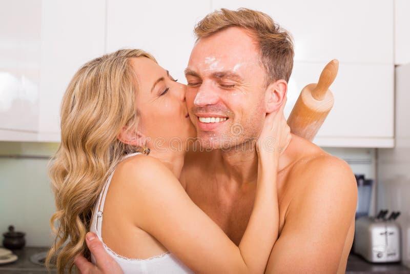 Γυναίκα που φιλά τον άνδρα της στο μάγουλο στην κουζίνα στοκ εικόνες