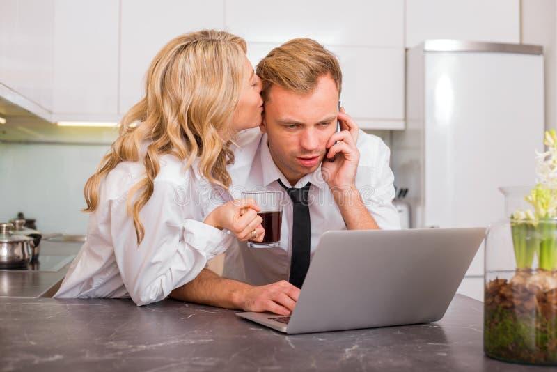 Γυναίκα που φιλά το σύζυγό της στο μάγουλο ενώ μιλά στο τηλέφωνο στοκ εικόνες