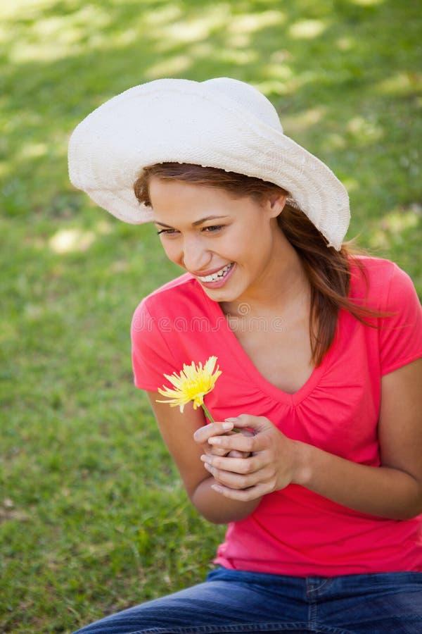 Γυναίκα που φορά ένα άσπρο καπέλο κρατώντας ένα κίτρινο λουλούδι στοκ φωτογραφίες
