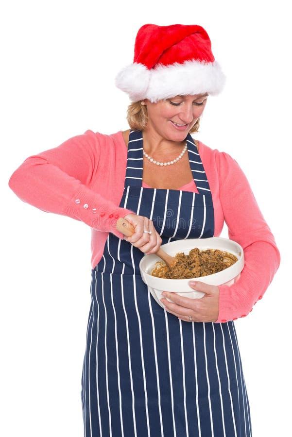 Γυναίκα που φορά ένα καπέλο Santa που κατασκευάζει ένα κέικ Χριστουγέννων στοκ εικόνα