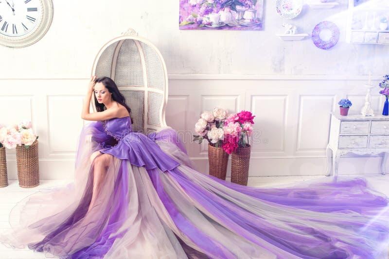 Γυναίκα που φορά πολύ την πορφυρή τοποθέτηση φορεμάτων στο εσωτερικό στούντιο στοκ εικόνα