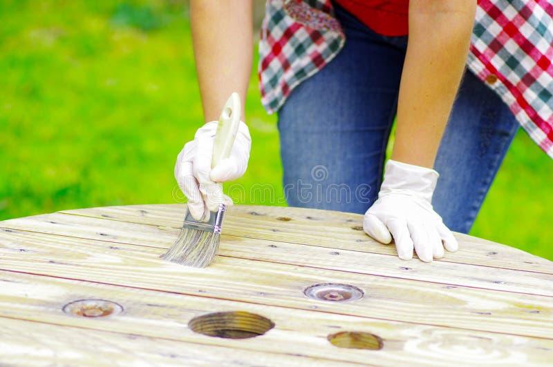 Γυναίκα που φορά τα γάντια που καθαρίζουν έναν ξύλινο πίνακα με μια βούρτσα στοκ φωτογραφία με δικαίωμα ελεύθερης χρήσης