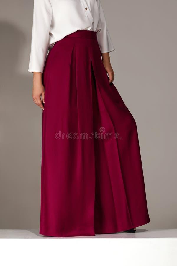 Γυναίκα που φορά τα υψηλά βαλμένα τακούνια παπούτσια burgundy στο παντελόνι στοκ φωτογραφίες