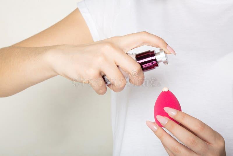 Γυναίκα που φορά την άσπρη μπλούζα που εφαρμόζει το υγρό ίδρυμα σε ένα σφουγγάρι makeup στοκ φωτογραφία με δικαίωμα ελεύθερης χρήσης