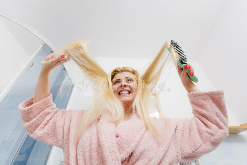 Γυναίκα που φορά την εσθήτα επιδέσμου που βουρτσίζει την τρίχα της στοκ φωτογραφία