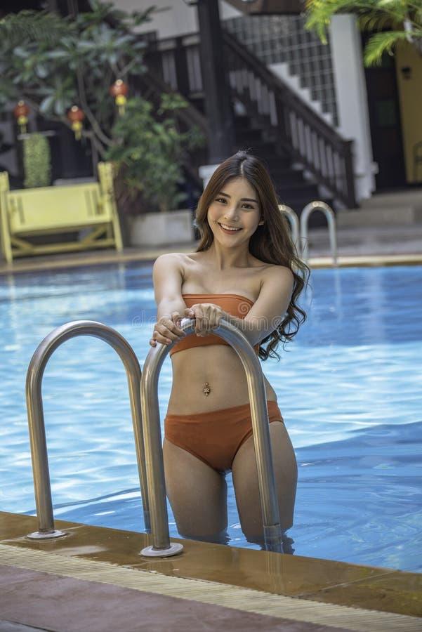 Γυναίκα που φορά την κομψή τοποθέτηση μπικινιών εκτός από την πισίνα στοκ εικόνες
