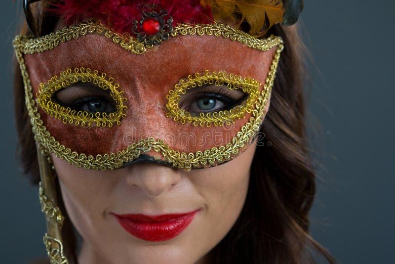 Γυναίκα που φορά τη μάσκα μεταμφιέσεων στο μαύρο κλίμα στοκ εικόνες με δικαίωμα ελεύθερης χρήσης