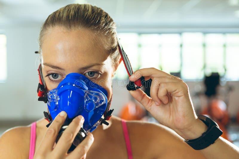 Γυναίκα που φορά τη μάσκα οξυγόνου πριν από την άσκηση στο κέντρο ικανότητας στοκ εικόνα με δικαίωμα ελεύθερης χρήσης