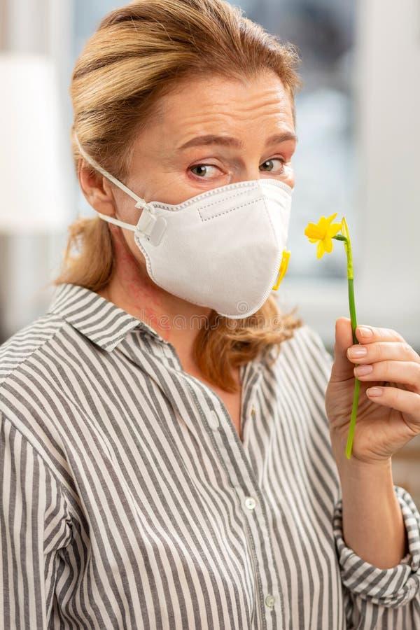 Γυναίκα που φορά τη μάσκα στο πρόσωπο που έχει την αλλεργία στα λουλούδια στοκ εικόνες
