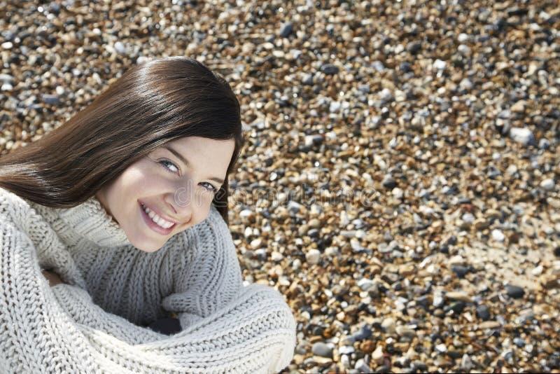 Γυναίκα που φορά τη συνεδρίαση πουλόβερ στην παραλία στοκ εικόνες