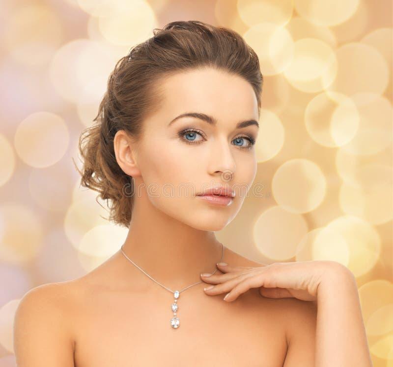 Γυναίκα που φορά το λαμπρό κρεμαστό κόσμημα διαμαντιών στοκ φωτογραφία