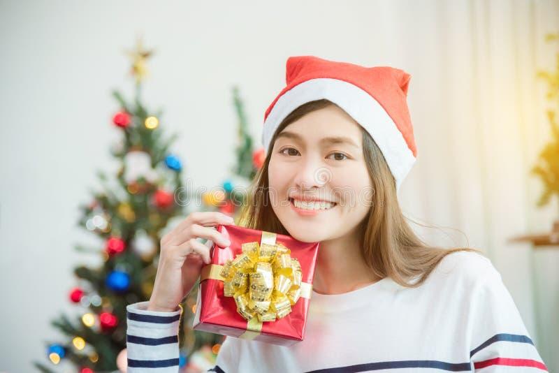 Γυναίκα που φορά το καπέλο Άγιου Βασίλη και που κρατά το δώρο Χριστουγέννων στοκ φωτογραφία με δικαίωμα ελεύθερης χρήσης