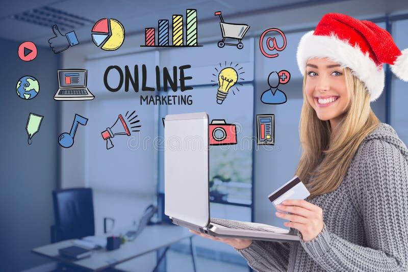 Γυναίκα που φορά το καπέλο Santa ψωνίζοντας on-line στοκ φωτογραφίες