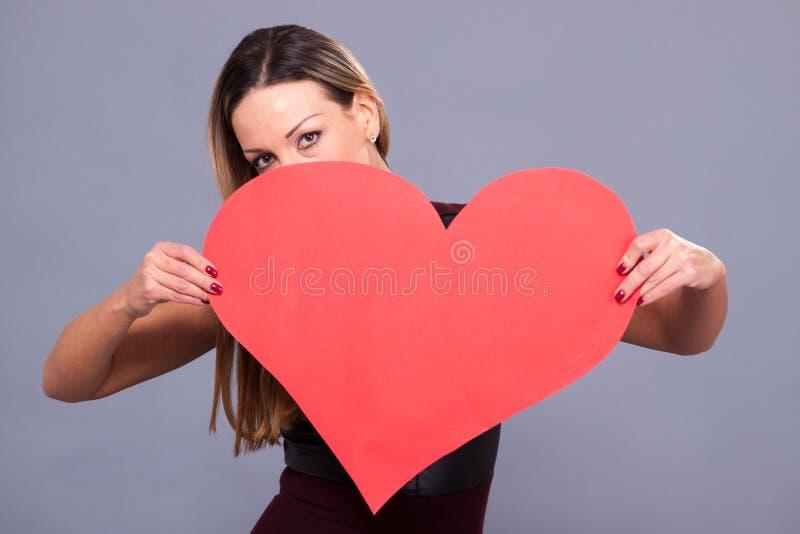 Γυναίκα που φορά το κόκκινο φόρεμα που κρατά το μεγάλο σύμβολο αγάπης σημαδιών καρδιών στοκ φωτογραφίες