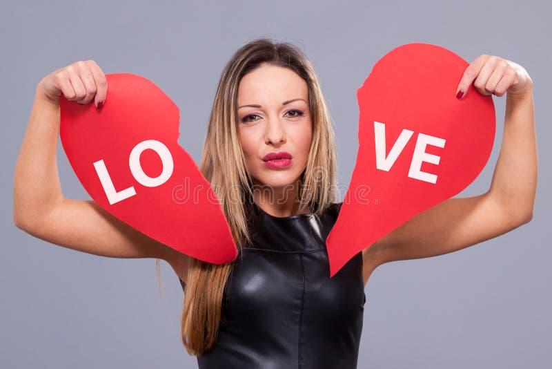 Γυναίκα που φορά το κόκκινο φόρεμα που κρατά το μεγάλο σύμβολο αγάπης σημαδιών καρδιών στοκ φωτογραφίες με δικαίωμα ελεύθερης χρήσης