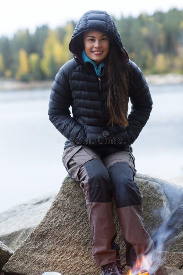 Γυναίκα που φορά το χειμερινό σακάκι κατά τη διάρκεια της στρατοπέδευσης όχθεων της λίμνης στοκ εικόνες με δικαίωμα ελεύθερης χρήσης