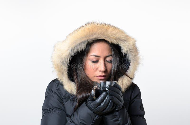 Γυναίκα που φορά το χειμώνα ΚΑΠ που πίνει το καυτό ποτό στοκ εικόνες