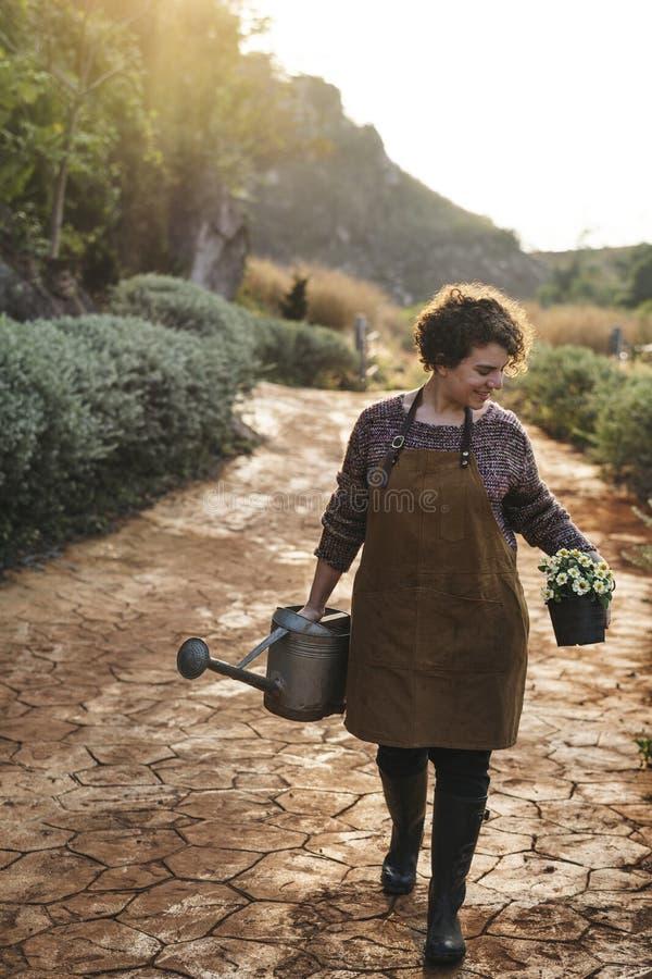 Γυναίκα που φροντίζει τα λουλούδια στο σπίτι επαρχίας της στοκ εικόνα με δικαίωμα ελεύθερης χρήσης
