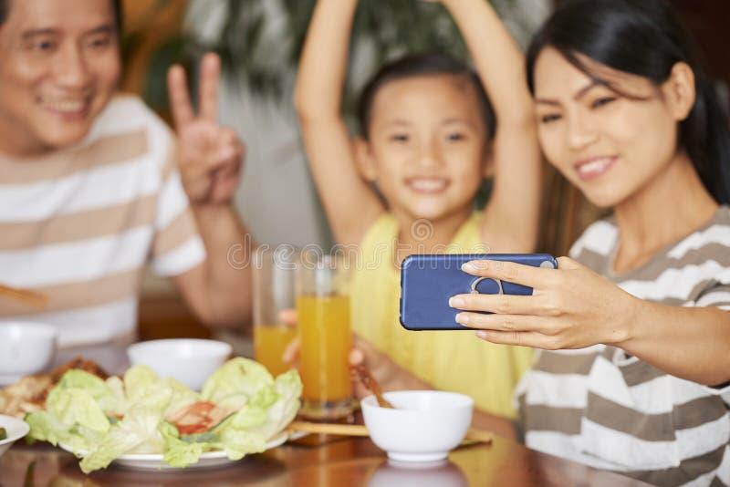 Γυναίκα που φωτογραφίζει με την οικογένεια στοκ εικόνες