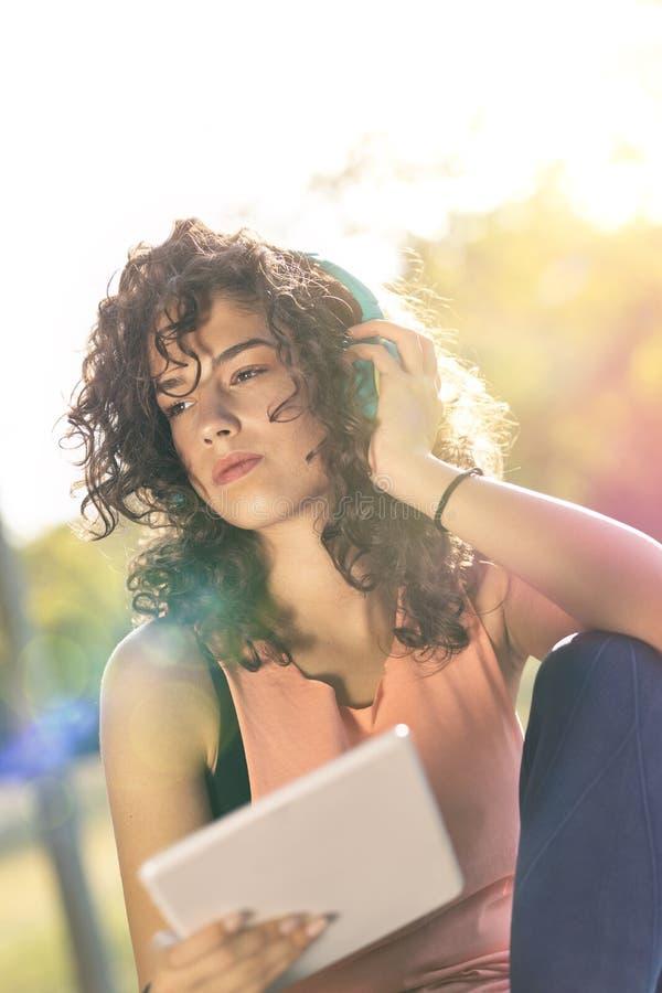 Γυναίκα που χαλαρώνει στο πάρκο χρησιμοποιώντας υπολογιστή tablet στοκ φωτογραφίες