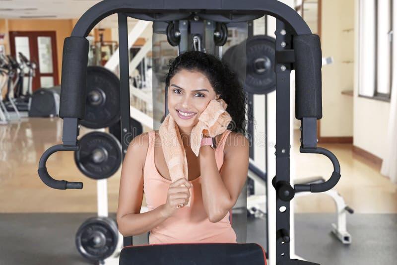 Γυναίκα που χαμογελά στη κάμερα σκουπίζοντας τον ιδρώτα στοκ εικόνες