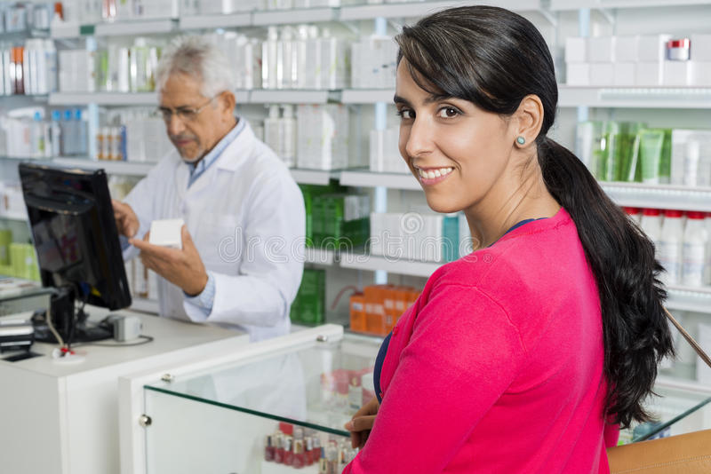 Γυναίκα που χαμογελά ενώ φαρμακοποιός που εργάζεται στο φαρμακείο στοκ φωτογραφίες με δικαίωμα ελεύθερης χρήσης