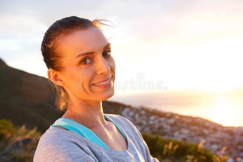 Γυναίκα που χαμογελά μπροστά από την ανατολή στοκ φωτογραφία με δικαίωμα ελεύθερης χρήσης