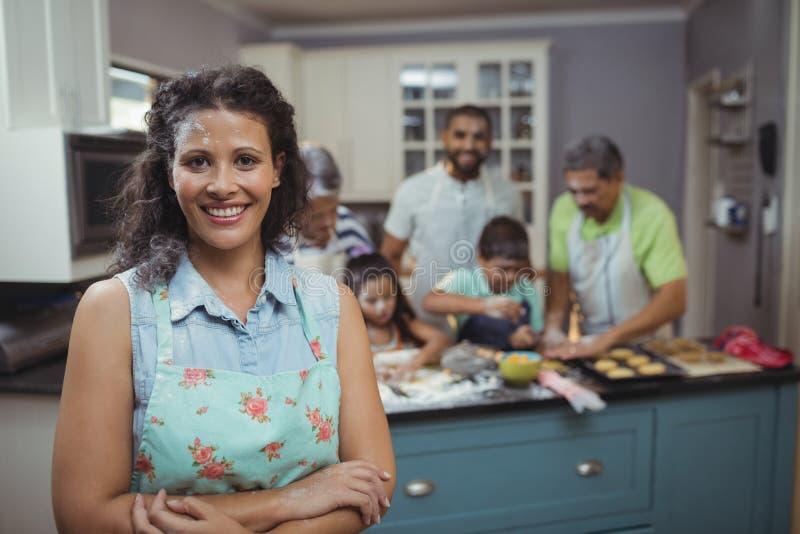 Γυναίκα που χαμογελά στη κάμερα ενώ οικογενειακά μέλη που προετοιμάζουν το επιδόρπιο στο υπόβαθρο στοκ φωτογραφίες με δικαίωμα ελεύθερης χρήσης