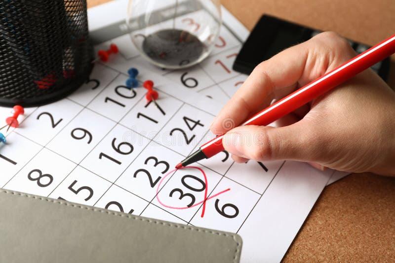 Γυναίκα που χαρακτηρίζει την ημερομηνία στο ημερολόγιο, κινηματογράφηση σε πρώτο πλάνο Έννοια προθεσμίας στοκ φωτογραφία