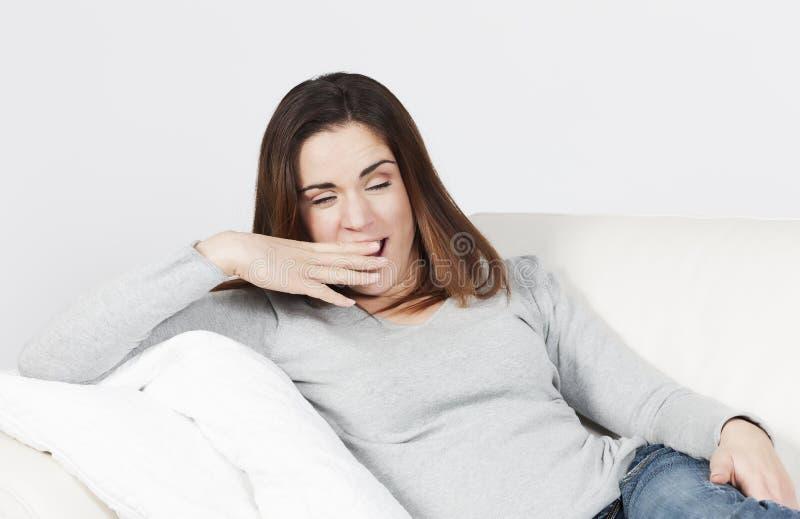 Γυναίκα που χασμουριέται στον καναπέ στοκ φωτογραφία με δικαίωμα ελεύθερης χρήσης