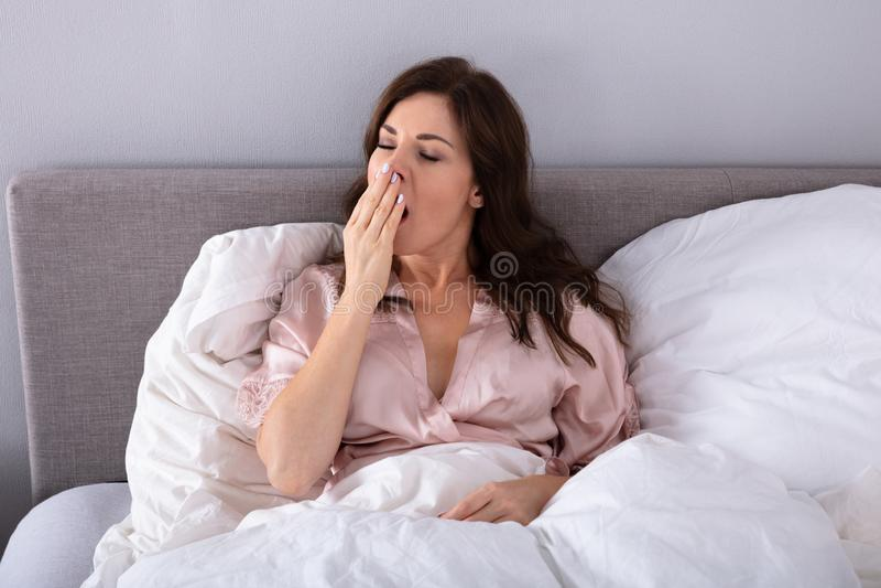 Γυναίκα που χασμουριέται στο κρεβάτι στοκ φωτογραφία με δικαίωμα ελεύθερης χρήσης